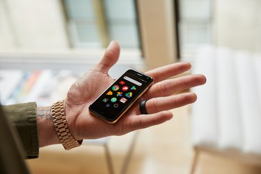 Man's hand holding tiny Palm smartphone