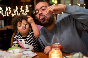 Father and young daughter eating off spoons together