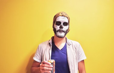 Man dressed as ghost holding can against yellow wall