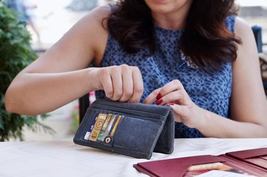 Woman going through open wallet to pay check at restaurant