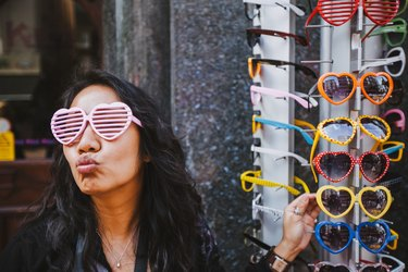A pretty young woman posing with heart-shaped sunglasses