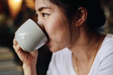 East Asian woman drinking coffee from cup