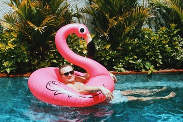 Man relaxing in a tropical pool on a pink flamingo floaty