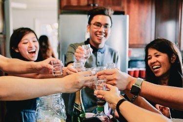 Millennials toast with shot glasses and laugh together