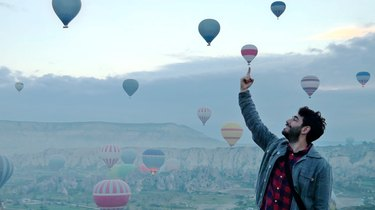 Bearded man posing against scene of hot air balloons