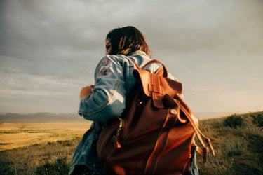 Young woman hiking Western landscape at sunset with backpack