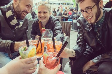 Hip young people toasting with mixed drinks