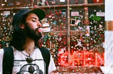 Young man blowing bubblegum in urban scene