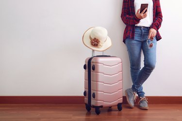 Asian woman traveler looking at smart phone, carry pink luggage with hat