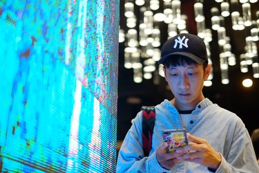 Young man using smartphone next to oversized neon LED light screen