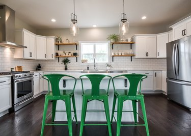 Farmhouse style modern kitchen staged with three green chairs