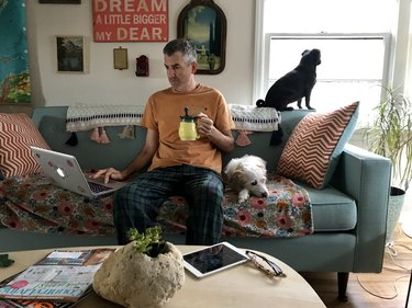 Man in pajamas with dogs, laptop and mug on couch