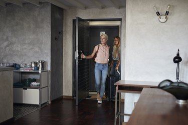 Two young woman arriving to urban rental apartment