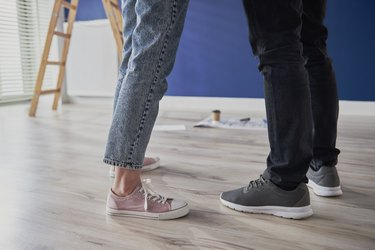 Legs of couple standing in new apartment