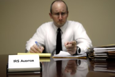 A male IRS tax auditor at a desk with paperwork