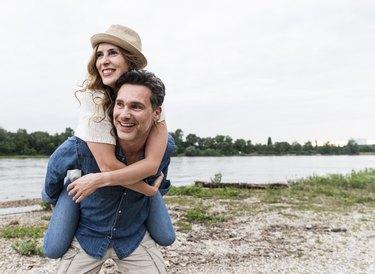 Happy man carrying girlfriend piggyback at the riverside