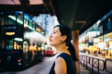 Young Asian woman traveller visiting and exploring busy city street in downtown Hong Kong