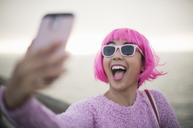 Young woman with pink hair taking a selfie