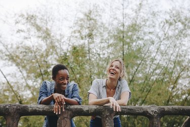 Two young female adult friends outdoors friendship bonding, freedom and outdoor concept