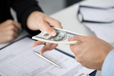 Woman taking batch of hundred dollar bills