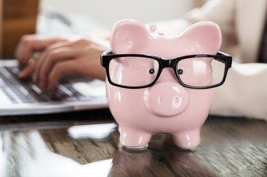 Pink Piggy Bank With Black Eyeglasses On Office Desk