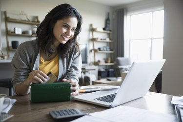 Smiling young woman with credit card and laptop paying bills online in dining room