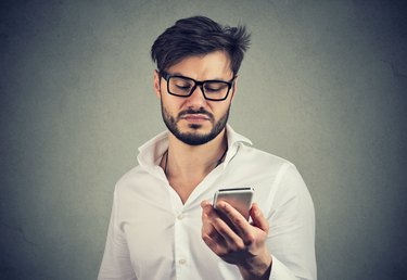 Angry disgusted man using smartphone