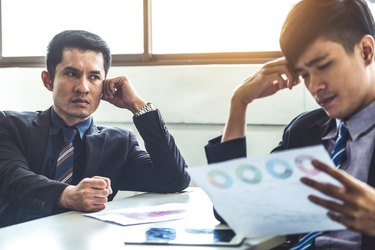 Unhappy business manager and young businessman partner in meeting room at the office. They are under stress because of bad financial document report. Company crisis concept.