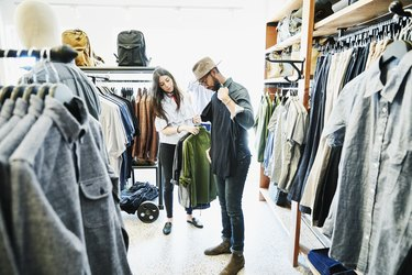 Shopkeeper helping man decide on shirts while shopping in mens clothing boutique