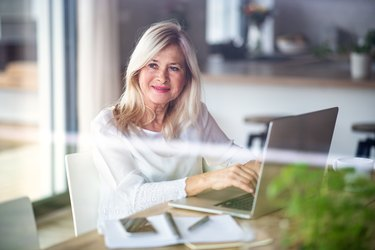 Senior woman with laptop indoors in home office, working.