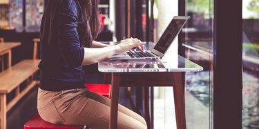 Beautiful young Asian girl working at a coffee shop with a laptop.female