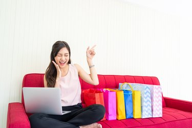 Portrait of young woman using laptop for online shopping on sofa and pointing fingers to empty space.