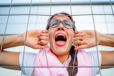 Young Woman Screaming Through Fence Due To Restraining Order