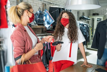 Shop owner receives wireless contactless payment from a customer who is shopping in the mall after reopening stores after COVID-19