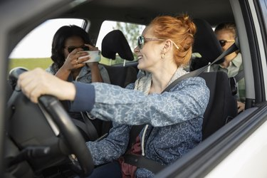 Young women friends in car with camera phone, enjoying road trip