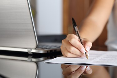 Woman hand writing a contract with a laptop beside