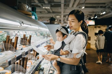Young Asian mother carrying cute baby girl shopping for fresh organic fish products in a supermarket