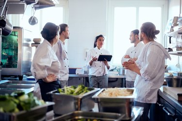 Mid adult female chef holding digital tablet while discussing with team in kitchen