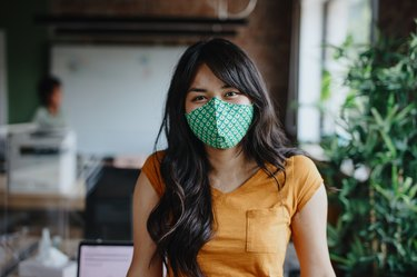 Portrait of businesswoman with cloth face mask after returning back to work