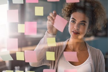 Young businesswoman brainstorming with adhesive notes on a glass wall