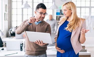 Coworker explaining something to pregnant woman