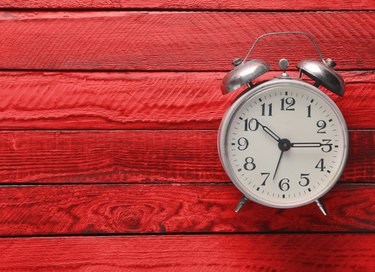 Vintage alarm clock on red wooden background. Top view.