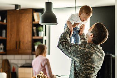 Playful military man having fun with his small son at home.