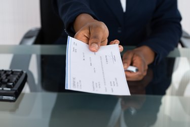 Person's Hand Giving Cheque