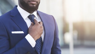 Bearded Afro Businessman Adjusting Tie In Urban Area, Cropped