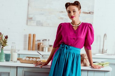 Stylish pin up girl in crimson dress and blue apron standing near kitchen table with various products