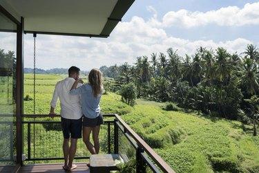 Couple standing on balcony, enjoying the landscape