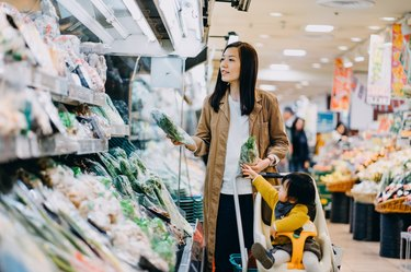 Cute little daughter sitting in a shopping cart grocery shopping for fresh organic vegetables with young Asian mother in a supermarket