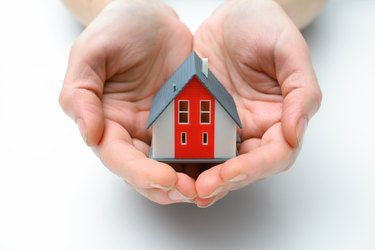 How to Sell My House to a Family MemberRed and gray model house in cupped hands on white background