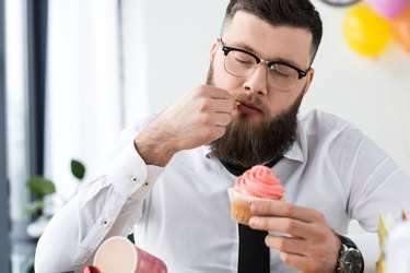 portrait of businessman holding birthday cupcake in hands in office